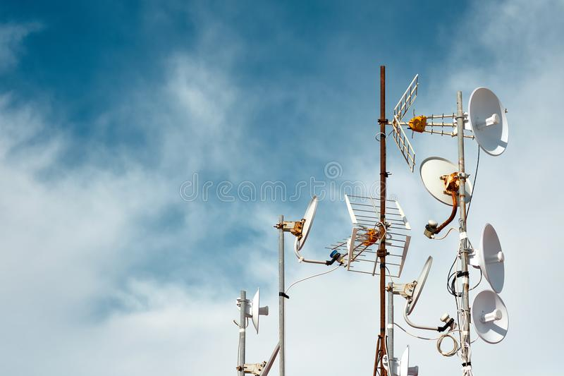 Antennas on a roof. Against cloudy sky background stock photos
