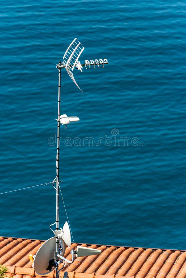 Antennas on the roof of a house by the sea stock photo