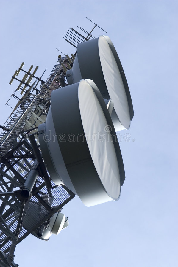 Antennas in the sky. Telecommunications antennas rise high against the blue sky royalty free stock image