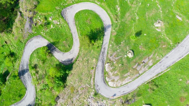 Antenne: übersteigen Sie hinunter Ansicht Tailspin über Wicklungsgebirgsstraße auf den italienischen Alpen, grünen der Wiese der  stockbild