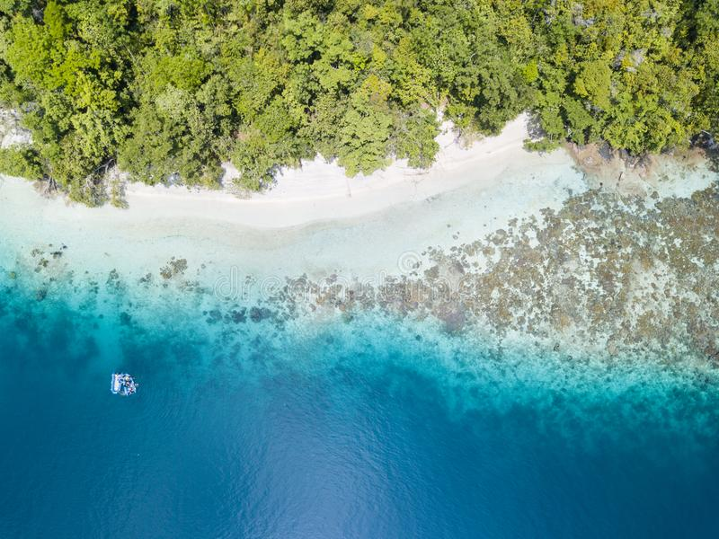 Antenne de forêt tropicale et récif de bordage en Raja Ampat photos stock