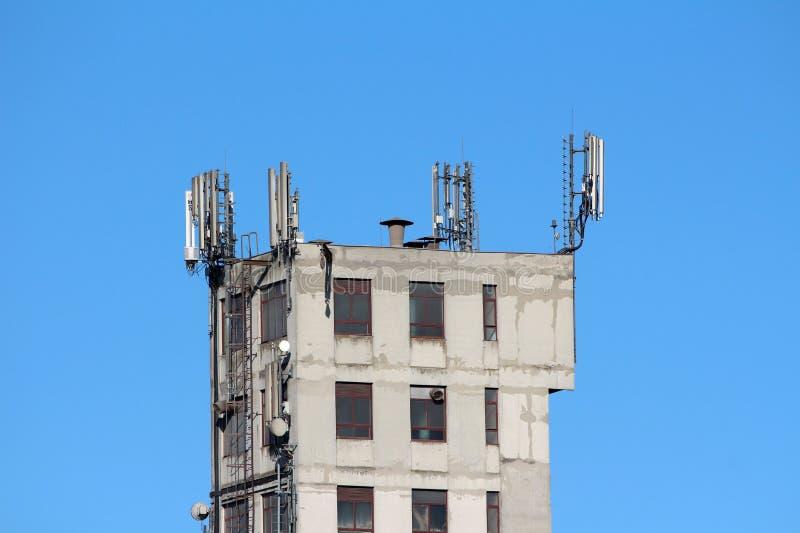 Antenne del telefono cellulare e trasmettitori sopra vecchio fabbricato industriale dilapidato con i punti del metallo su un lato fotografie stock libere da diritti