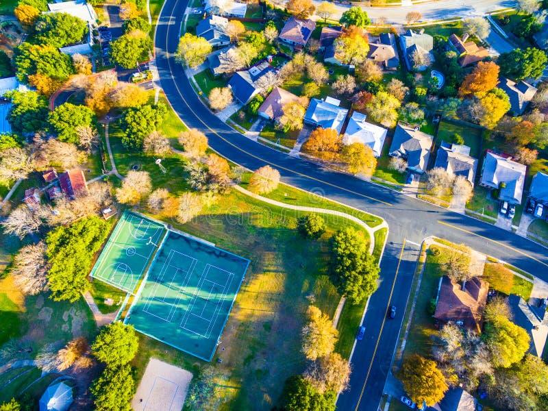 Antenne die onderaan over Modern Austin Texas Countryside Community Suburbia Neighborhood met Tennisbanen en Recreatief Gebied ki stock foto's