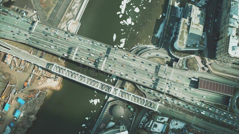 Antenne hinunter Ansicht von den Autos, die entlang die Brücke über eisigem Fluss sich bewegen stockfoto