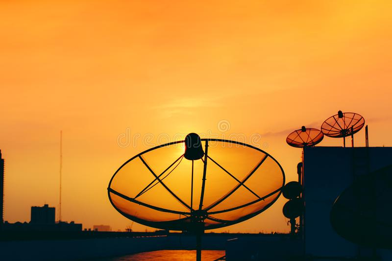 Antenne parabolique sur le bâtiment avec la télévision numérique de coucher du soleil de ciel image stock