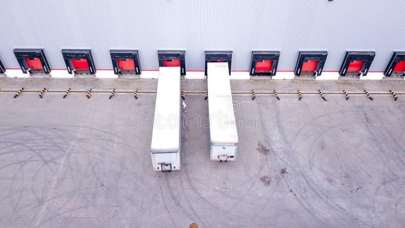 Antenne van het Industri?le Dok wordt geschoten van de Pakhuislading waar velen Vrachtwagen met Semi Aanhangwagens Koopwaar die l stock fotografie