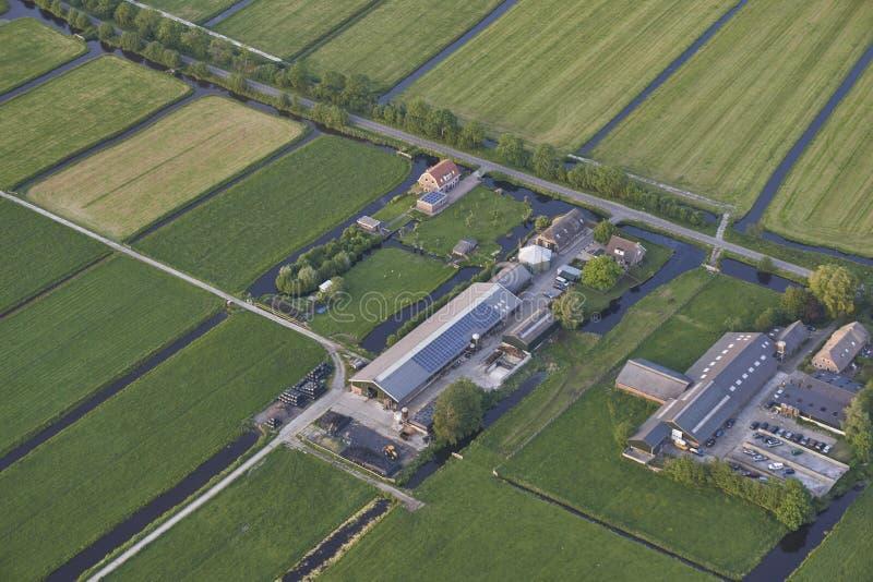 Antenne van moderne landbouwbedrijven met zonnepanelen op het dak in Nederlands weidelandschap royalty-vrije stock fotografie