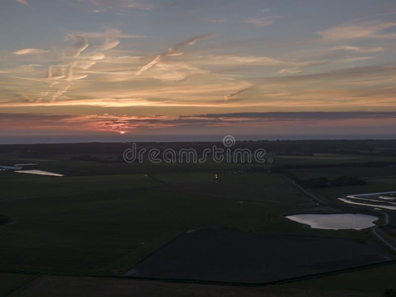 Antenne van zonsondergang over landbouwmeadowland en overzees op het Nederlandse Eiland Texel royalty-vrije stock afbeeldingen