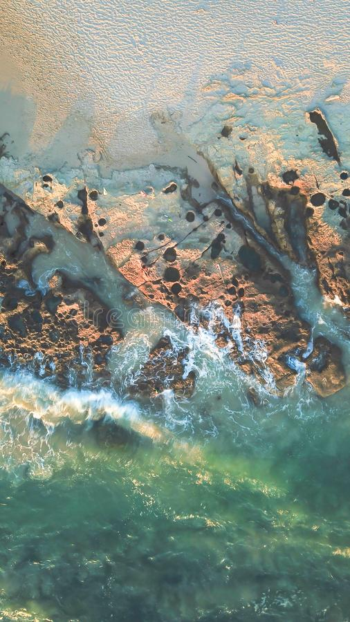 Antenne von den Wellen, die Felsen auf dem Strand schlagen lizenzfreie stockfotos