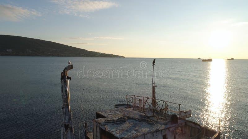Antenne voor schipbreuk op een strand met blauwe, bewolkte hemel en groene bergachtergrond schot Gesloopte verlaten boot stock afbeelding