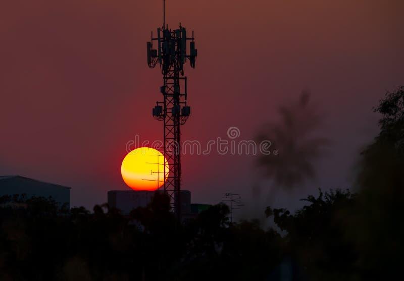 Antennen för telekommunikationer och stor solnedgångbakgrund är kontur- och värmeväder arkivfoto