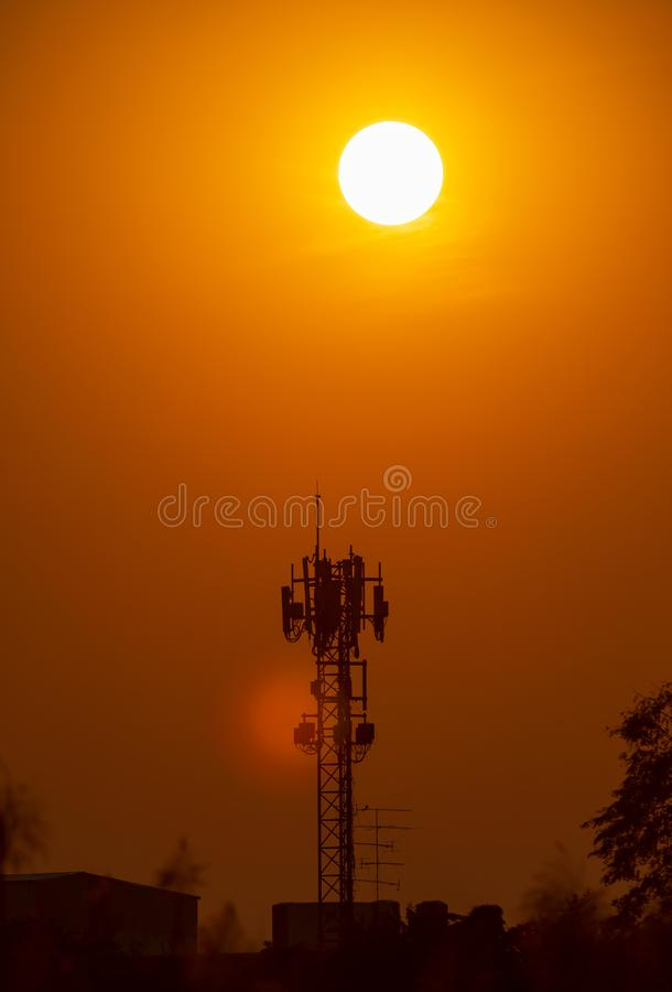 Antennen f?r telekommunikationer och stor solnedg?ngbakgrund ?r kontur- och v?rmev?der royaltyfri foto