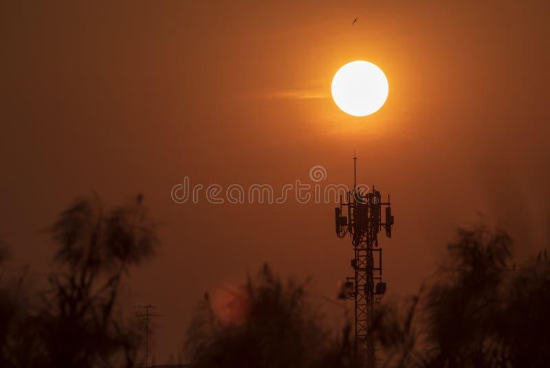 Antennen f?r telekommunikationer och stor solnedg?ngbakgrund ?r kontur- och v?rmev?der royaltyfri bild