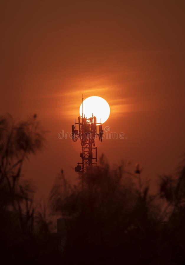 Antennen f?r telekommunikationer och stor solnedg?ngbakgrund ?r kontur- och v?rmev?der royaltyfria foton