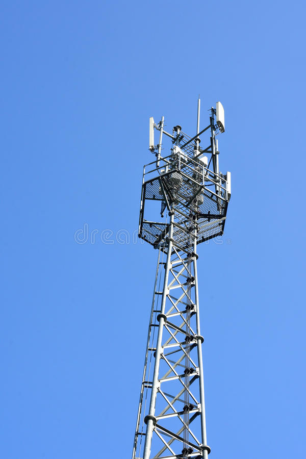Antennetoren van Mededeling over blauwe hemel stock foto's