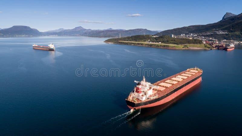 Antennskott av ett lastfartyg på det öppna havet med andra skepp och berg i bakgrunden royaltyfria foton