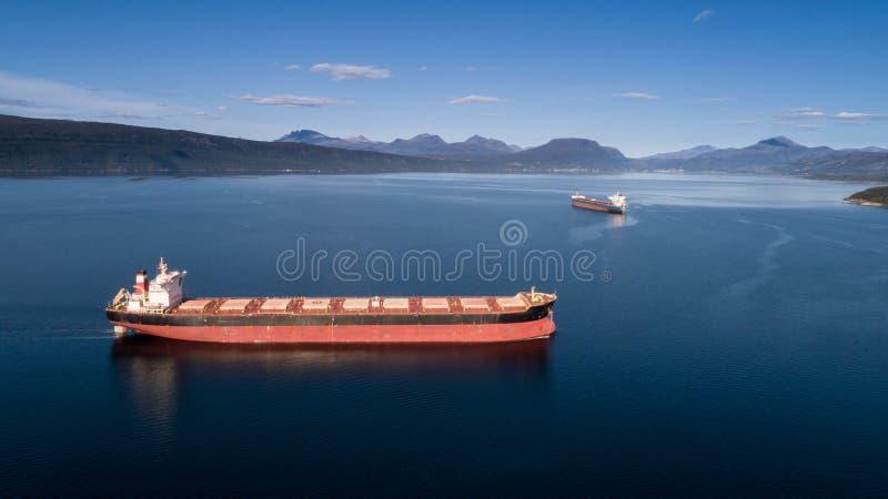 Antennskott av ett lastfartyg på det öppna havet med andra skepp och berg i bakgrunden royaltyfri fotografi