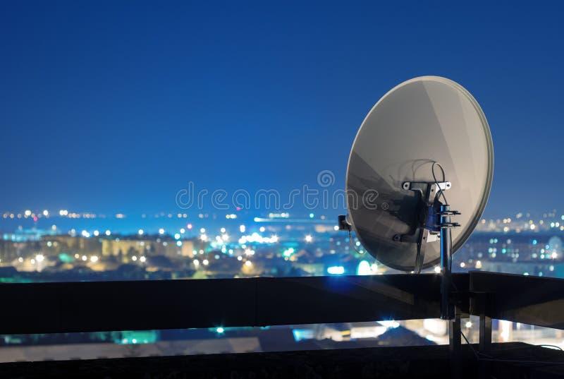 Anteny satelitarnej antena na górze budynku przy nocą zdjęcie royalty free
