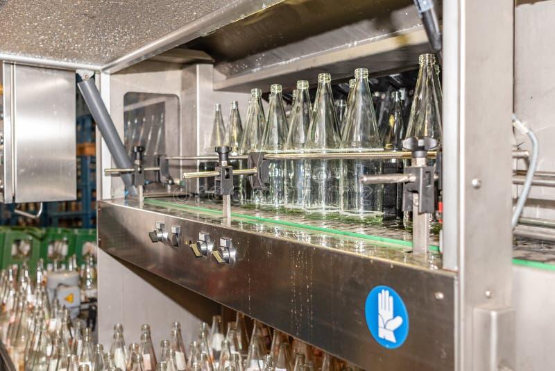 Antes de llenar las botellas de la bebida se limpian en un lavaplatos industrial especialmente para las botellas de cristal imagen de archivo
