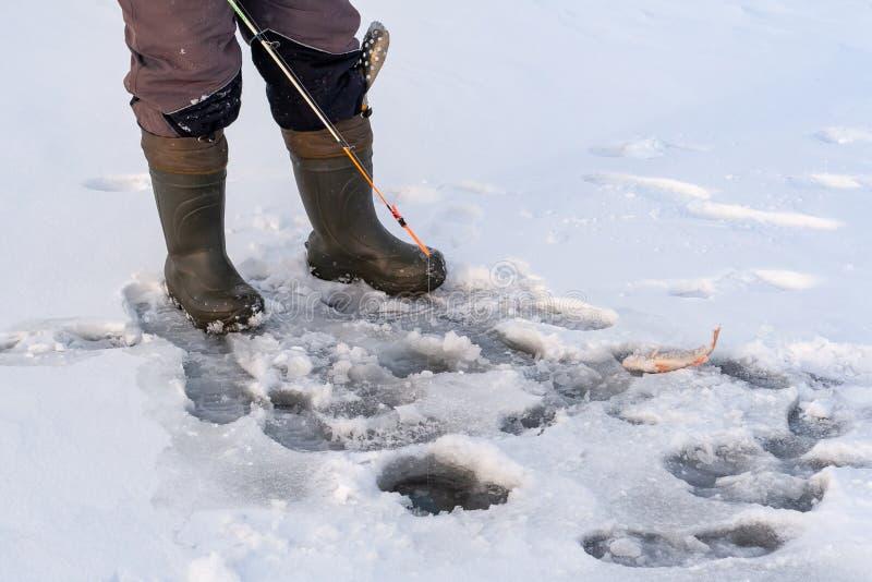 Antes do furo para a pesca do inverno, simplesmente os pés do pescador fotografia de stock