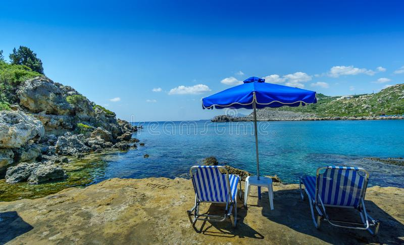 Anthony Quinn Bay secluded beach with umbrella and chairs. A bright sunny day at the secluded beach of Anthony Quinn bay. A view at the valley and the sea behind stock photo