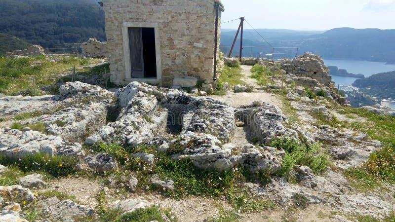 Anthropomorphic gravar och bysantinskt kapell överst av Angelocastro, Korfu arkivfoton