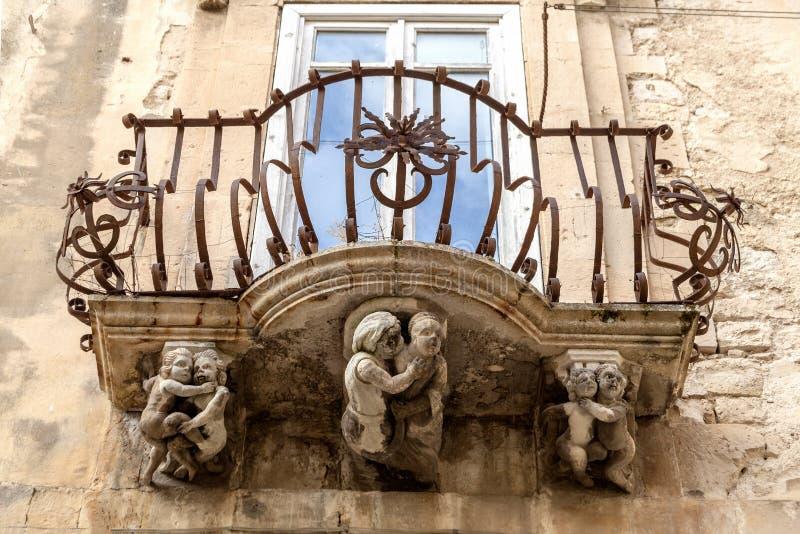 Anthropomorphic Stone figures under the balcony of La Rocca palace. Ragusa Ibla Sicily Italy stock photography