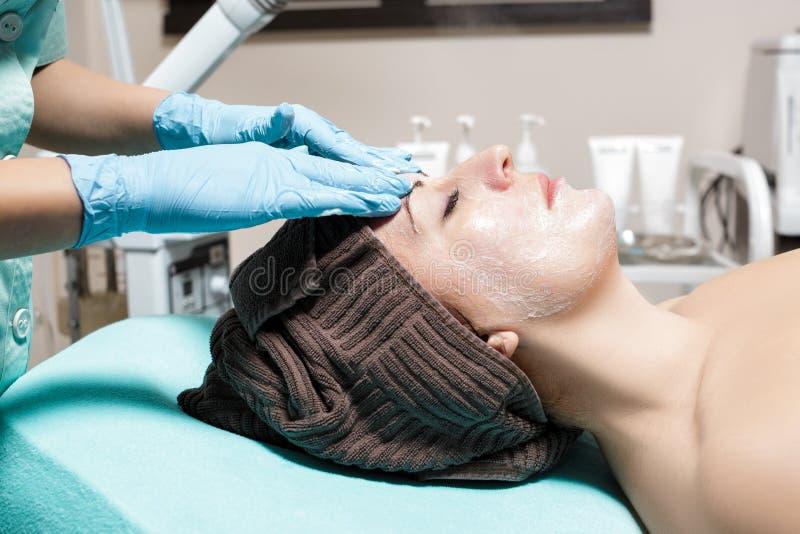 Anti--åldras ansikts- massage cosmetologist som gör massagen för ung kvinna på den Spa salongen arkivfoton