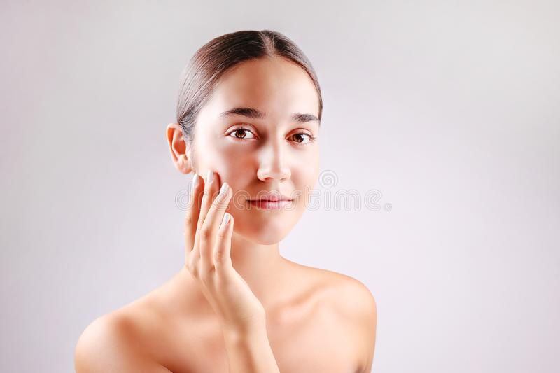 Anti acne and wrinkle skincare cream concept, brunette girl with satisfied facial expression stock images