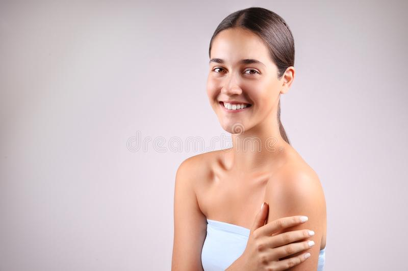 Anti acne and wrinkle skincare cream concept, brunette girl with satisfied facial expression stock photo