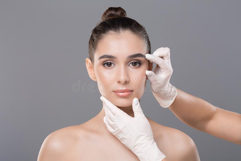 Beautician hands in gloves examining woman face. Anti age beuty procedures. Beautician hands in gloves examining woman face, close up royalty free stock images