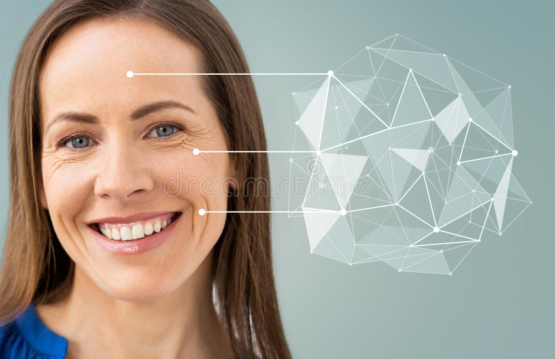 Middle aged woman with pointers on her face. Anti-age, people and beauty concept - beautiful middle aged woman with low poly shape and pointers on her face over stock images