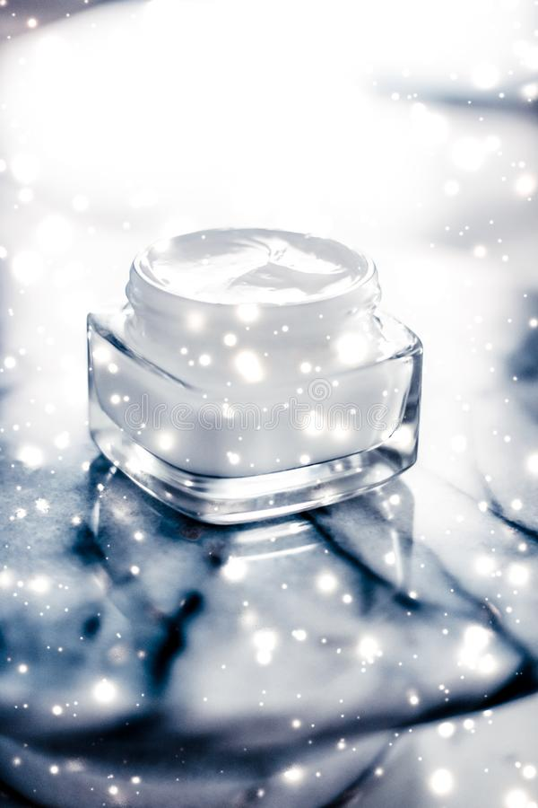 Magic beauty face cream and glitter glow on blue marble stone in winter holiday time, skincare moisturizer and luxury spa. Anti-age product, facial care and royalty free stock photos