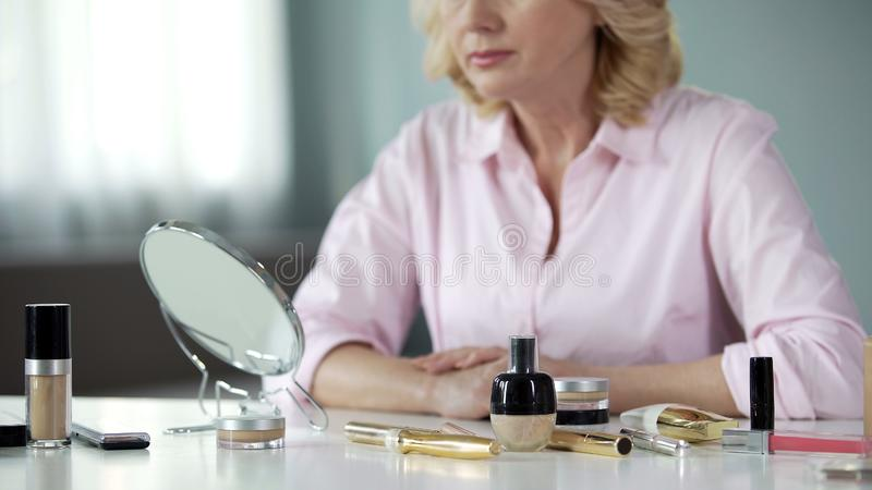 Anti-aging cosmetics on table with senior woman on background, beauty care. Stock photo stock photos