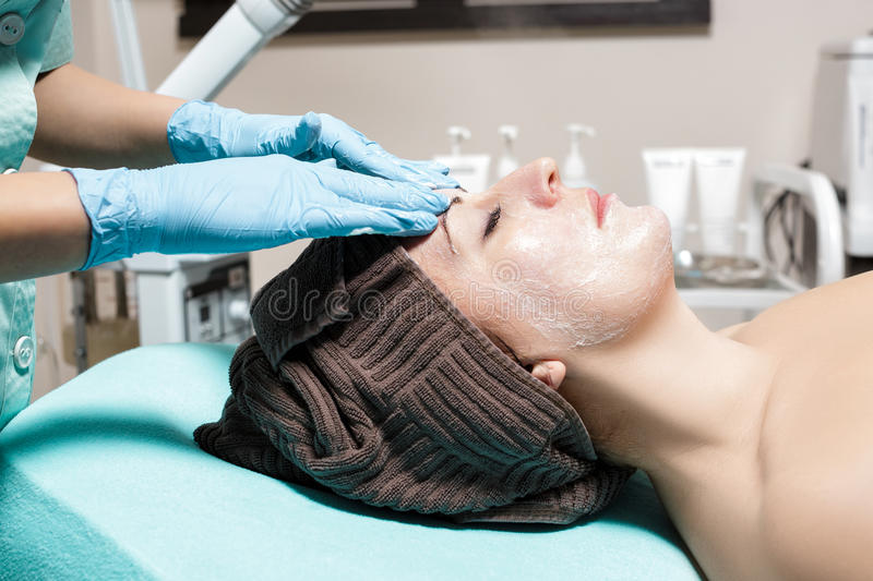 Anti-aging facial massage. cosmetologist doing massage for young woman at Spa salon. stock photos