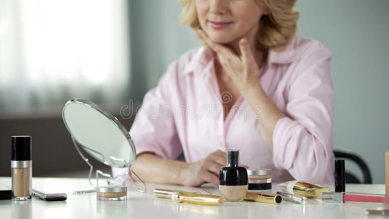 Anti-aging make-up products with mature lady looking in mirror behind, beauty. Stock photo stock images
