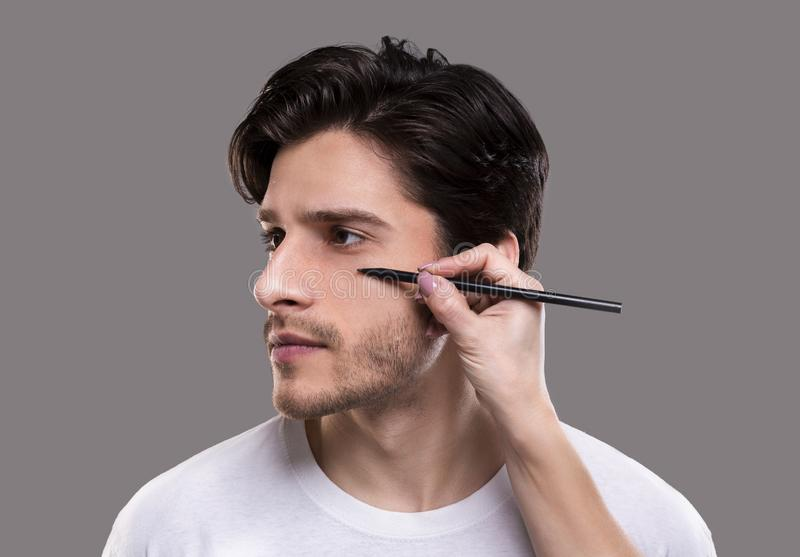 Plastic surgeon drawing guide marks on male patient face royalty free stock images