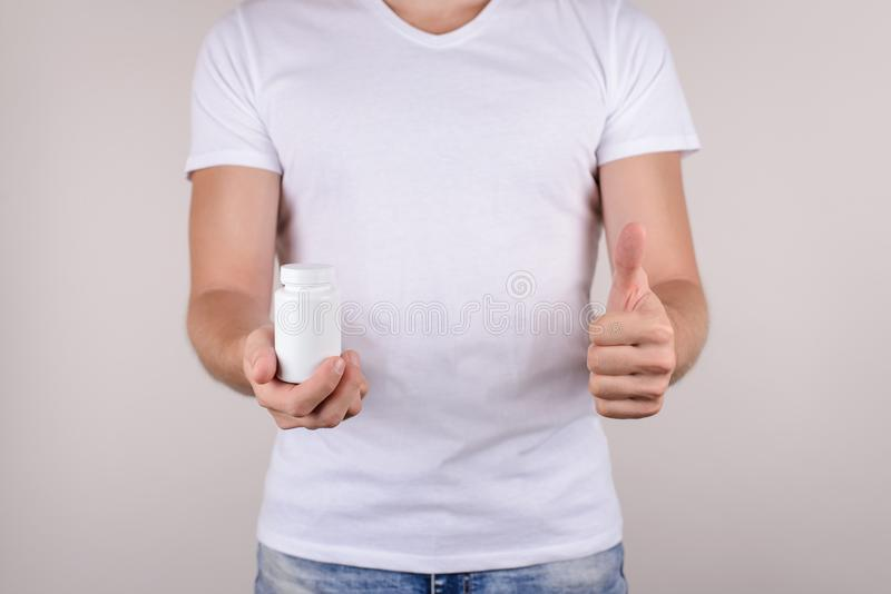 Anti allergy painkiller concept. Cropped close up photo of happy glad confident cheerful guy in denim jeans making giving finger u stock image