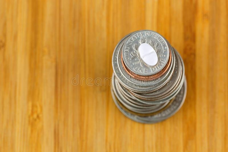 Anti anxiety white pill medicine on stack of American US coins o stock image