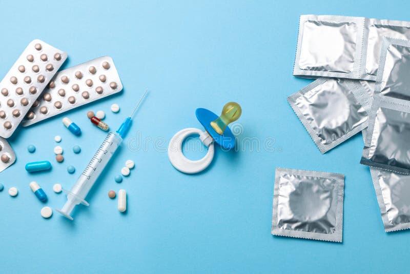 Anti-Baby-Pillen, eine Injektionsspritze und Kondom in einem Paket auf Blau Das Konzept des Wählens von Methode der Empfängnisver stockfotografie