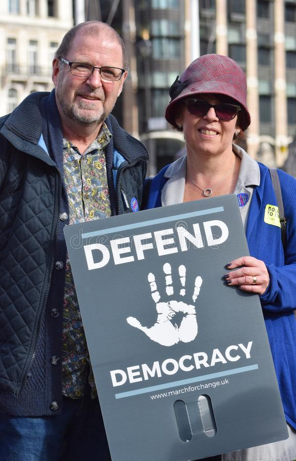 "Anti Brexit demonstrators / protesters in London on October 19 2019. Protestors in London with a board that reads ""Defend Democracy"" - which is a royalty free stock photography"