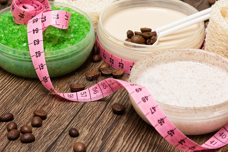 Anti cellulite cosmetic products with body measuring tape royalty free stock photo