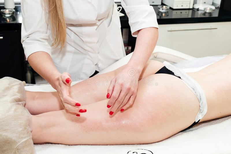 Anti-cellulite massage of buttocks area, woman legs receiving massage in beauty salon. Cellulite treatment, skin care, wellbeing, royalty free stock photo