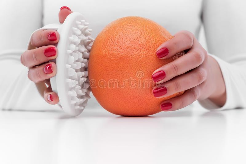 Anti-cellulite massager and orange. stock image