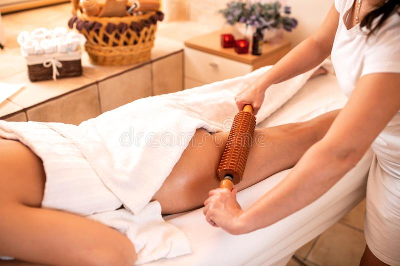 Anti-cellulite treatment with a help of a wooden roller. Maderotherapy stock photos