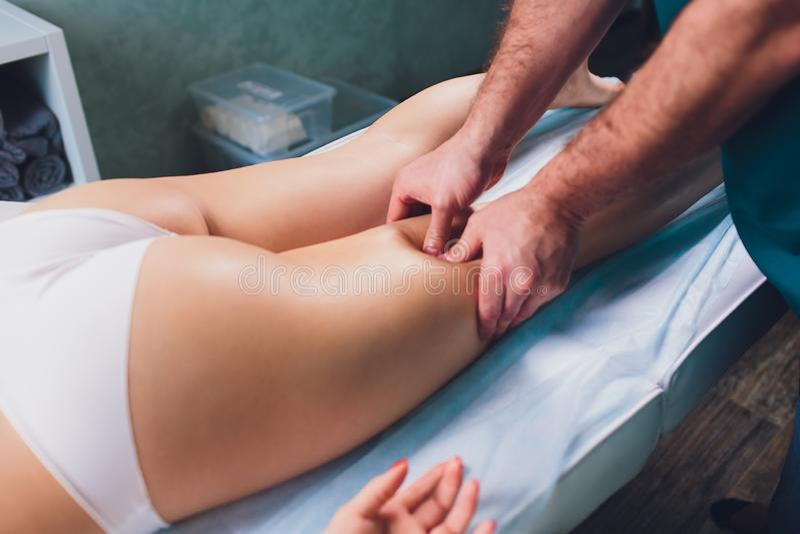 Anti-Cellulitemassage auf den Beinen von jungen Frauen stockfotografie