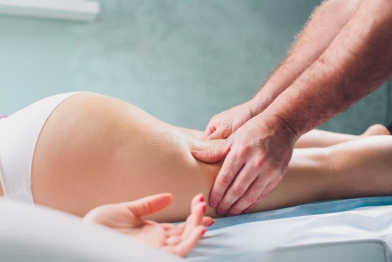 Anti-Cellulitemassage auf den Beinen von jungen Frauen stockfoto