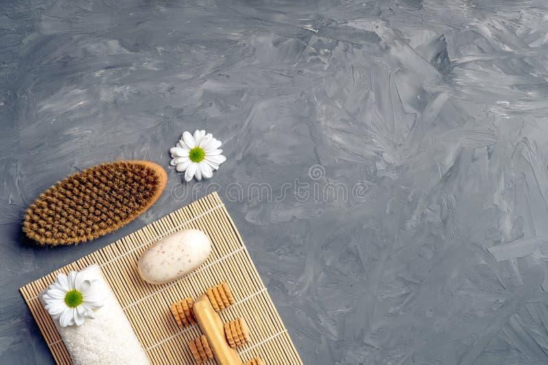 Anti-cellulitemassagetillbehör och kosmetiska produkter för brunnsortskönhet på grå färgstenbakgrund från över Lekmanna- lägenhet fotografering för bildbyråer