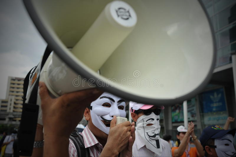 Anti-Government Protest in Bangkok. A masked protester gives direction using a loud hailer during an anti-government rally in Bangkok's shopping district on July stock images