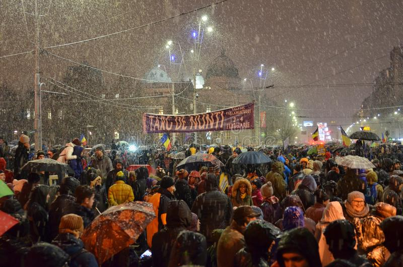 Anti government protests in Bucharest in inclement weather. Bucharest, Romania - January 20, 2018: People gathered in University Square, in the center of the stock photos